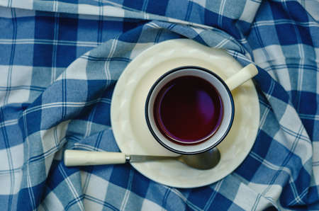 Top view: a cup of coffee, tea on a saucer and a teaspoon on a checkered napkin in blue and white. copyspace.