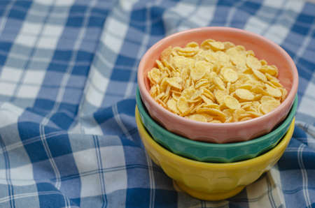 Cornflakes and three bowls of different colors, on a plaid napkin in blue and white. copy space.