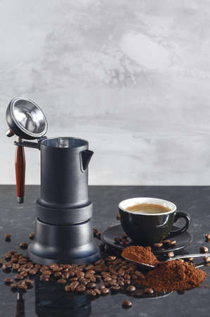Coffee maker Type geyser and black colored coffee cup, with coffee beans and freshly ground coffee in a spoon