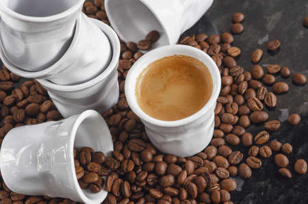 Ceramic cups look like crumpled paper espresso coffee cups and sprinkled roasted coffee beans
