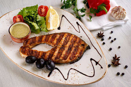 Grilled salmon steak, served with sauce, lemon, lettuce and tomatoes, on a white dish. Copyspace.