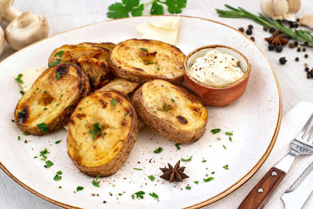 Rustic baked potato with cream sauce and spices on a serving platter. Copyspace.