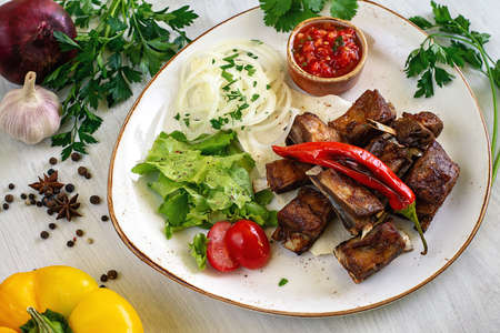 Lamb ribs on pita bread with salad and tomato sauce on a platter for serving. Copyspace. Stock fotó