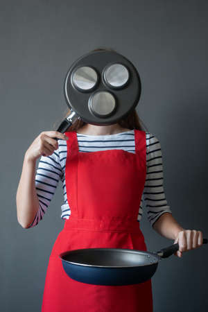 The image of a young woman in a cook apron covered her face with a frying pan for cooking fritters, holds the pan to the belt levels with her second hand 스톡 콘텐츠