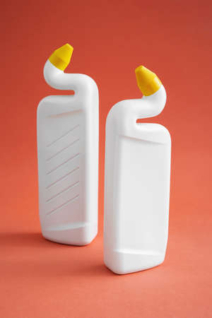 two white plastic bottles without labels with cleaning products on a pink background, toilet gel, two bottles with yellow dispenser caps