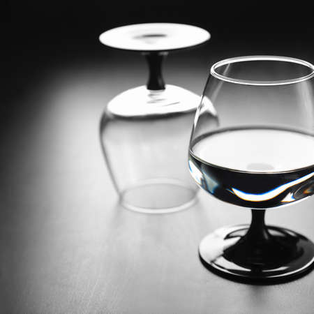 Two glasses on a black leg, one with water, the second turned upside down, against a dark background. Copyspace Stock Photo