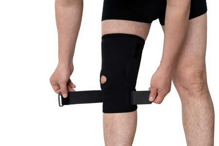 Orthosis on the male leg. A man fixes a black orthosis on his leg. Isolated on white background.