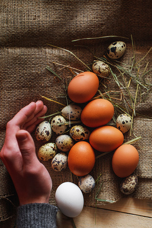 Fresh, raw eggs lie on the grass. Wood background. Texture of burlap. Organic background. Healthy eating. Easter composition.