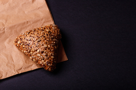 Fresh bread with sesame on paper. Triangle bun. Copy space