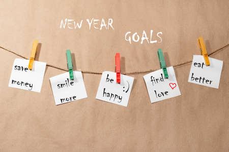 New Years goals. Stickers hanging on a rope attached with red and green clothespins, on a paper background