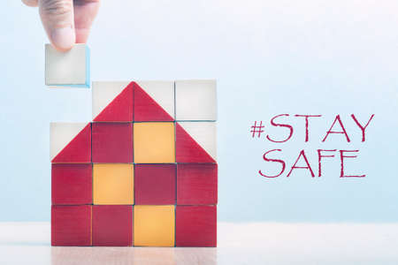 "Mosaic of children's cubes in the shape of a house. The hand puts the last cube. The label on the right is ""stay safe""."