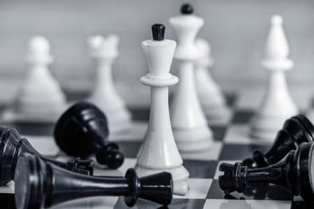 The concept of team success and corporate spirit. White chess pieces on the chessboard Around them lie the defeated black pieces. Foto de archivo