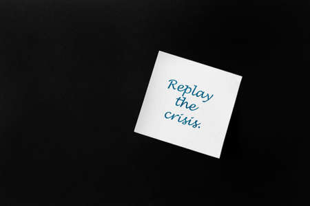 """On a black background, a white sticker with the inscription: """"Replay the crisis"""".The concept of anti-crisis development."""