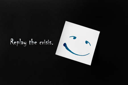 """On a black background, a white sticker with a drawn smiley face. To the left of the sticker is the inscription: """"Replay the crisis"""".The concept of anti-crisis development."""