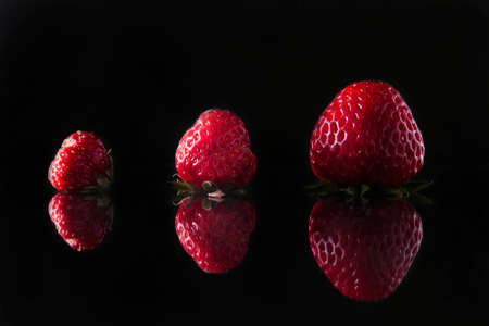 Concept of business development, career growth, motivational concept. On a black background, three red strawberries of different sizes.