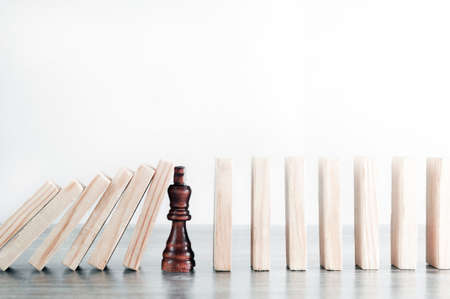 Motivational concept, concept of development, success, leadership, actions in a crisis situation. In the way of falling blocks, there is a chess piece that stops the fall. Foto de archivo