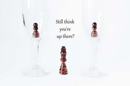 Motivational concept, the concept of development, success, leadership, getting out of the comfort zone. There are two pawns in two glasses. At the bottom, between the glasses, stands the king. Standard-Bild