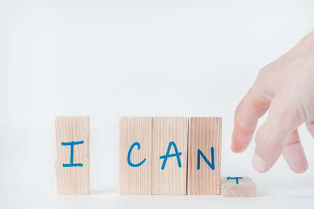 "Motivational concept, concept of development, success. The wooden blocks say ""I can't"". The hand removes the block labeled 't."