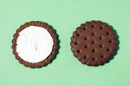 Two halves of chocolate-cream cookies on a pastel green background.