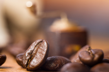 Coffee beans and a tiny coffee grinder miniature, close-up on wooden table