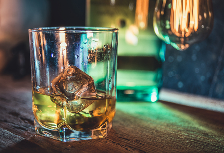 A glass of whisky on rough wooden background