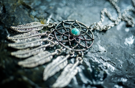 Tiny silver Dream Catcher amulet, an ancient magic talisman on stone background Reklamní fotografie