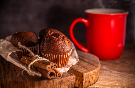 Fresh chocolate muffins and cinnamon sticks on rustic wooden background