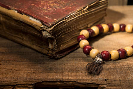 Spiritual still life, old book and wooden beads Stock Photo