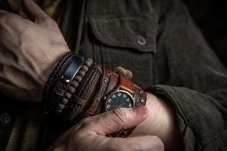 Stylish man wears wrist wooden and leather bracelets