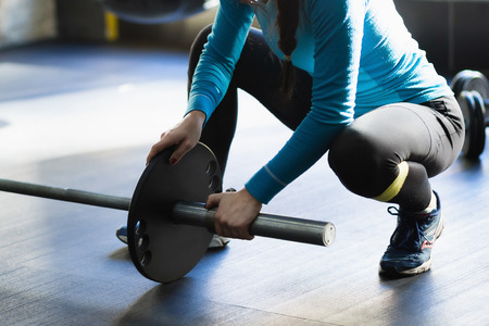 heavy weight: Muscular woman in a gym doing heavy weight exercises. Young woman doing weight lifting at health club. Stock Photo
