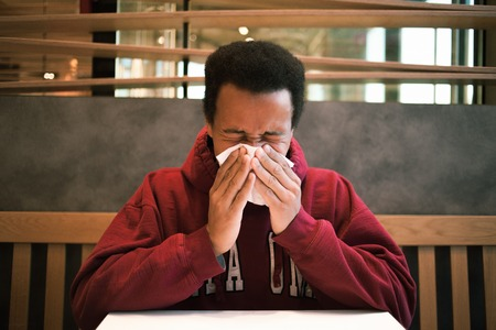 gagging: The dark-skinned man blowing his nose in a cafe. African American cold