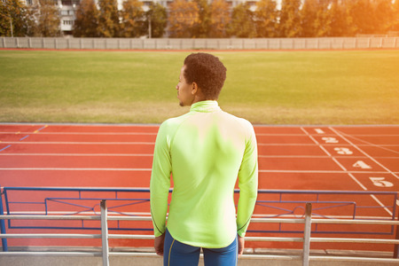 the stands: Sprinter stands in the stadium. The dark-skinned man in training