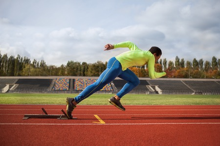 Afro-American man running around the stadium. Young sprinter on the track for jogging Stock Photo