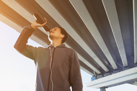 man drinking water: Athletic man drinking water in the city