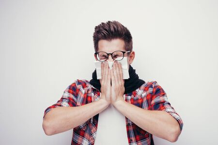 Attractive young man in red shirt and glasses got a cold. All isolated on white background. Stock Photo