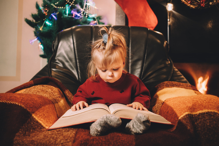 bedtime story: Little girl reading a bedtime story by the fireplace. Pre-christmas mood. New Years is soon