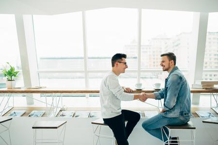 男性はモダンなカフェのテーブルに座って、手を振ってします。幸せな若い男は、契約を締結しました。彼らは良い取引をしました。