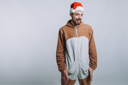 Young handsome man with noel or santa hat. Funny guy is wearing pajamas or fancy dress. Isolated on white background Stock Photo