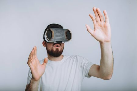 he is different: Young man trying vr goggles and imagining virtual reality doing different moves with hands. He is surprised because of seeing something marvellous. Isolated on white background Stock Photo