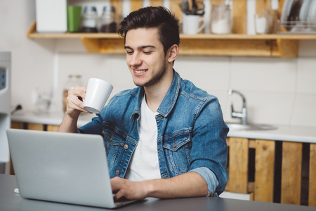 Young man with beard typing on laptop. He is sitting in the kitchen and smiling because of seen video. Happy boy is trying to drink some coffee