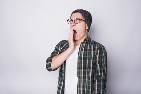 Young man standing on white background and yawning. He didnt sleep well previous night and now he is tired