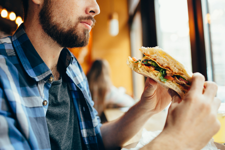 Man in a restaurant eating a hamburger Stock Photo