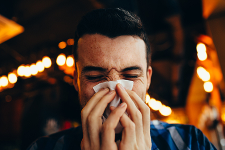 Attractive young man blowing his nose with his both hands. Poor guy got a cold. He is in restaurant or cafe. Close-up