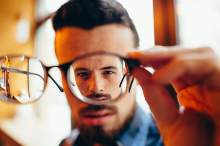 Closeup portrait of young man with glasses, who has eyesight problems Stock Photo