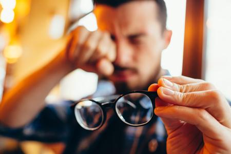 視力の問題は、眼鏡を持つ若い男のポートレート、クローズ アップ