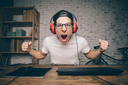 venganza: Young man playing game at home and streaming playthrough or walkthrough video. Stylish boy screaming because of fail. He is going to make revenge thats why he is holding his fists in attack position