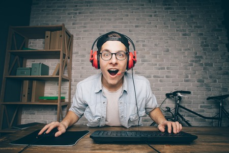 transmitting device: Young man playing game at home and streaming playthrough or walkthrough video. Stylish guy is surprised with one intresting game in vr. He is wearing eyeglasses, black cap and red headphones
