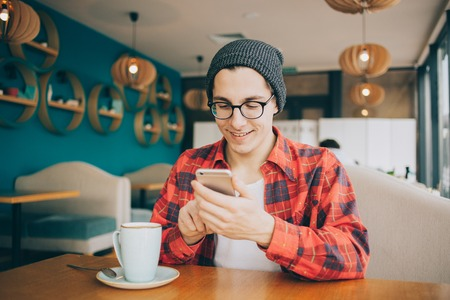 positiv: Attractive young man or freelancer is sitting in cafe and drinking tea.