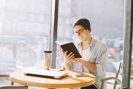 intresting: Handsome businessman in casual wear and eyeglasses is using a laptop. Young freelancer is sitting in cafe and holding a notebook filled with new ideas and goals. He is smiling and glad to have such a good inspiration or he is reading just interesting book Stock Photo