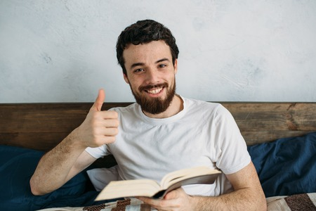 he: Bearded man in white shirt reading a big book lying in his bedroom. Happy guy is holding it with both hands. He is looking at the camera and showing thumb up. Close up